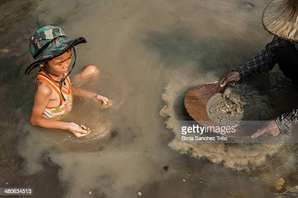 A child plays with the sand as his mother pans for gold on March 25 2014 in Lampang Thailand Thai villagers from Wang Nuea North of Thailand look for...