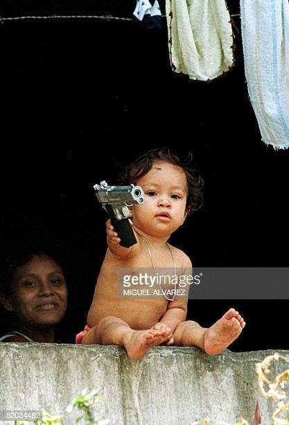 A child plays with toy pistol in a neighborhood where needy families live 16 September 1999 in Managua Un nino juega con una pistola de juguete el 16...