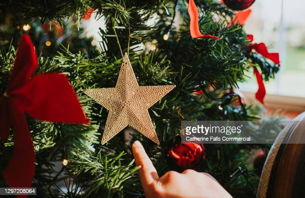 child pointing at a beautiful gold christmas star hanging on a christmas tree - symbolism stock pictures, royalty-free photos & images