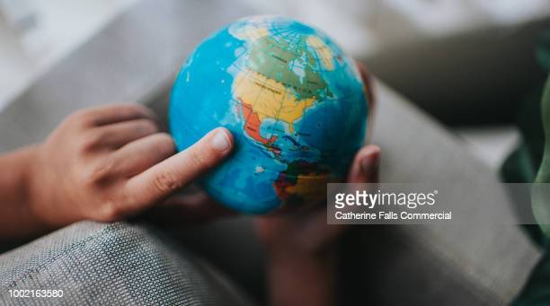 child pointing to a globe - emigration och immigration bildbanksfoton och bilder