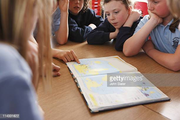 child pointing to country in atlas at school