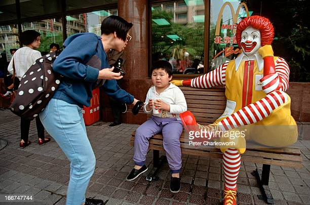 Ronald mcdonald getty images a child poses for a photo next to a ronald mcdonald statue outside of a large voltagebd Gallery