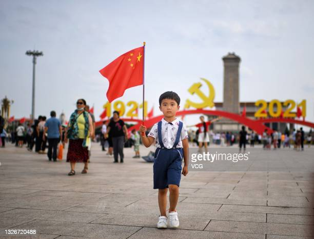 Child poses for photos in front of an art installation marking the 100th anniversary of the founding of the Communist Party of China at Tiananmen...