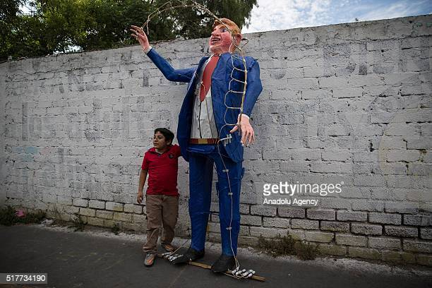 A child poses with a figure representing US Republican presidential candidate Donald Trump before being burned during the Saturday of Glory as part...
