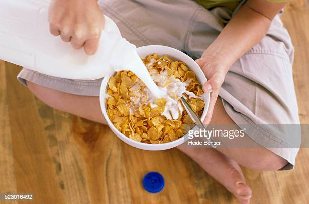 child pouring milk in cereal - milk carton stock photos and pictures