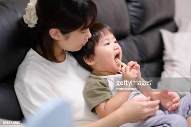 母親に歯を磨く方法を練習している子