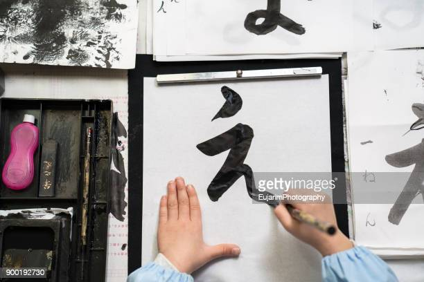 child practicing japanese calligraphy at home - sporting term stockfoto's en -beelden