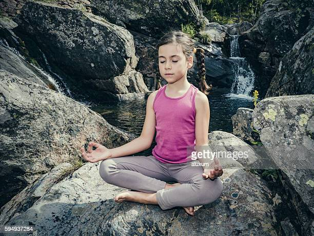 Child practicing meditation in nature