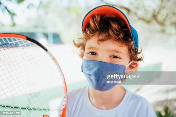 bambino che pratica il tennis sorridendo dietro la maschera di protezione del viso - praticare foto e immagini stock