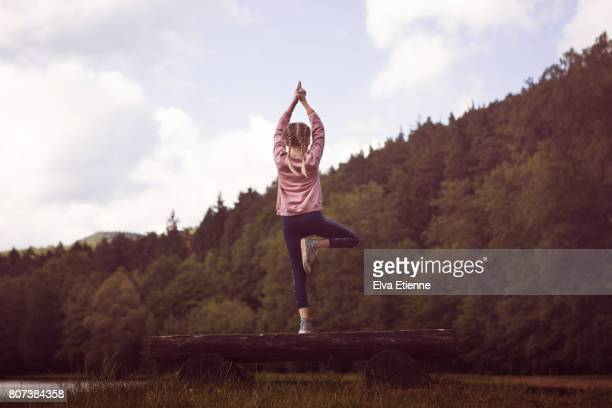 Child practising the tree yoga pose in a forest setting