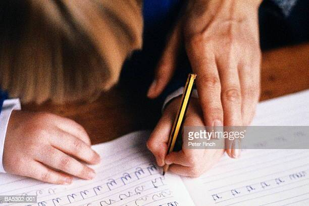 Child (5-7) practising writing in book, guided by adult, close-up