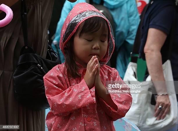 Child prays at the Hiroshima Peace Memorial Park on the day of the 69th anniversary of the atomic bombing of Hiroshima on August 6, 2014 in...
