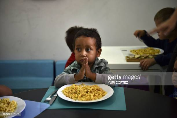TOPSHOT A child prays before eating at the Kapuy Foundation shelter which supports children in situation of abandonment or with serious health...