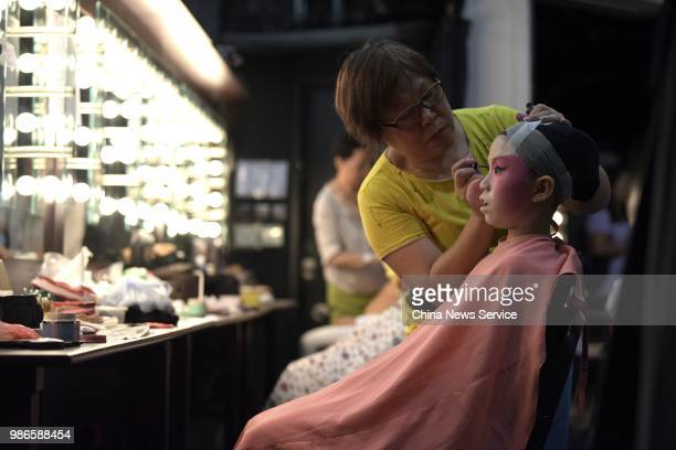 A child prepares backstage prior to a Cantonese opera performance on June 26 2018 in Hong Kong China Thirtyfour children from Po Leung Kuk Grandmont...