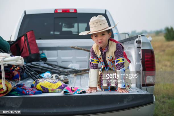 A child prepares for a parade at Crow Fair in Crow Agency Mont as Sen Jon Tester DMont greets constituents nearby on August 19 2018 Tester is being...