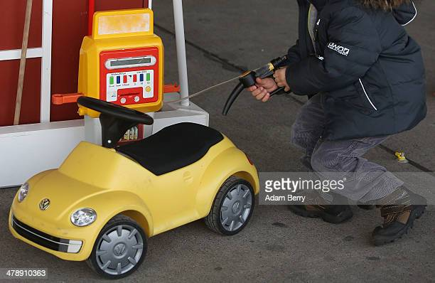 Child pretends to put fuel into a toy Volkswagen Beetle at the Electric Mobility Week , a public Volkswagen event at the former Tempelhof airport, on...