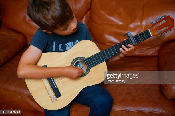 child prodigy playing acoustic guitar - musical symbol stock pictures, royalty-free photos & images