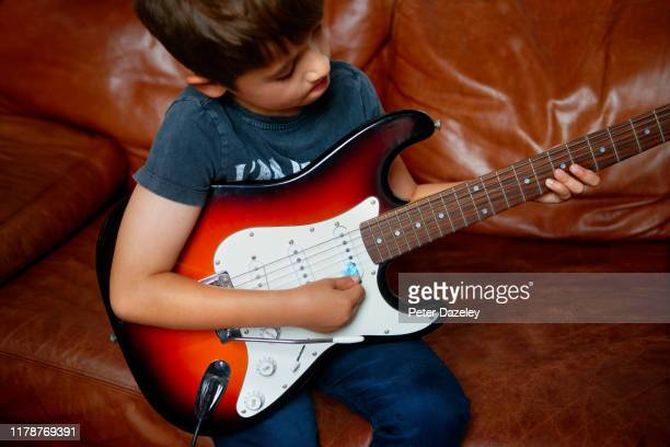 child prodigy playing electric guitar - man made object stock pictures, royalty-free photos & images