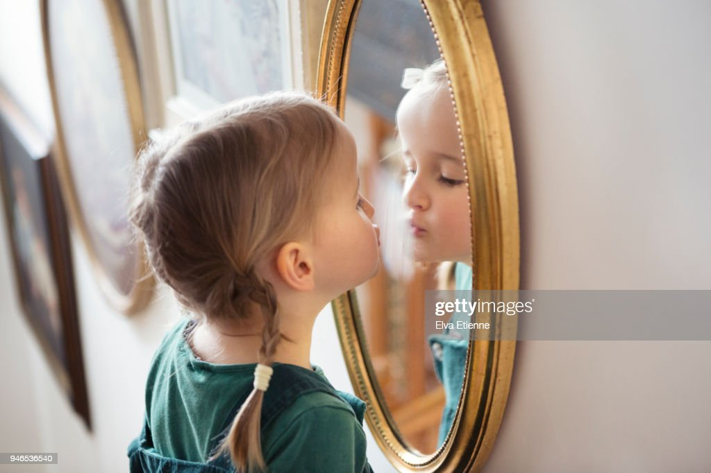 Child puckering up at her own reflection in a mirror, whilst steaming the glass with her breath : Stock Photo