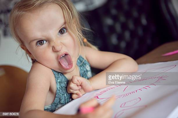 Child pulling a face whilst drawing