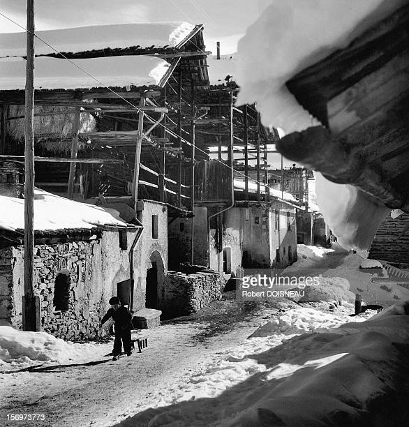 Child pulling a sledge in the Hautes-Alpes, 1947 in Saint Veran, France.