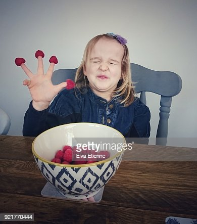 Child pulling a sour expression whilst eating raspberries