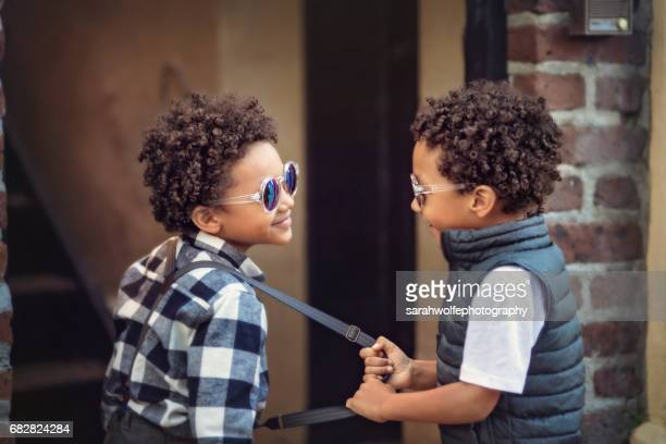 child pulling on his twin brother's suspender - downtown comedy duo stock pictures, royalty-free photos & images
