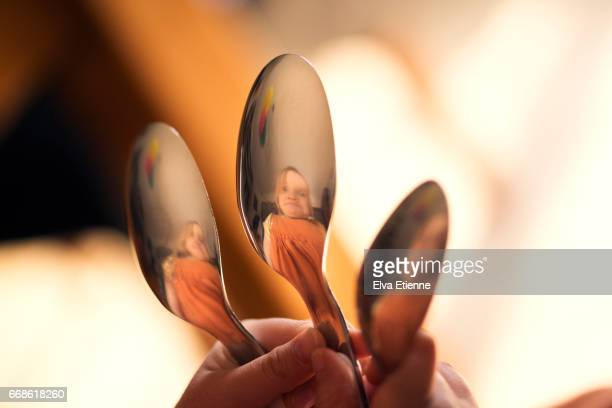 Child pulling silly face, reflected in spoons