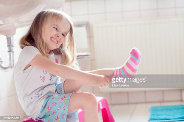child (4-5) pulling socks on with determined facial expression - grimacing stock pictures, royalty-free photos & images