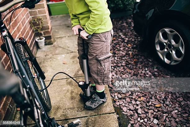 child pumping up bicycle tyre - air pump stock photos and pictures