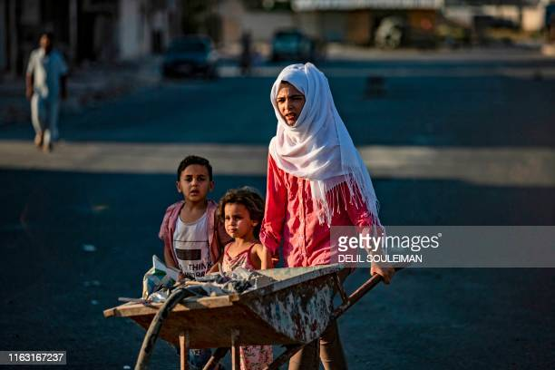 Child pushes a construction cart in the northern Syrian city of Raqa, the former Syrian capital of the Islamic State group, on August 21, 2019. - The...