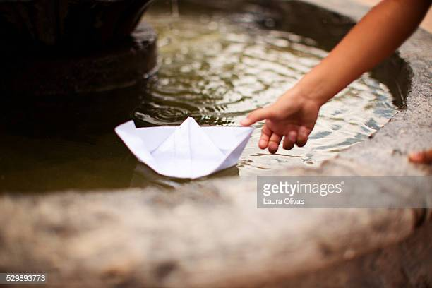 Child Pushes Paper Boat In A Fountain