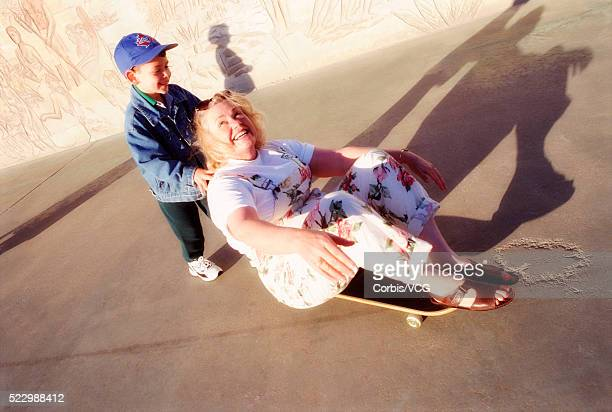 Child Pushing Woman on Skateboard