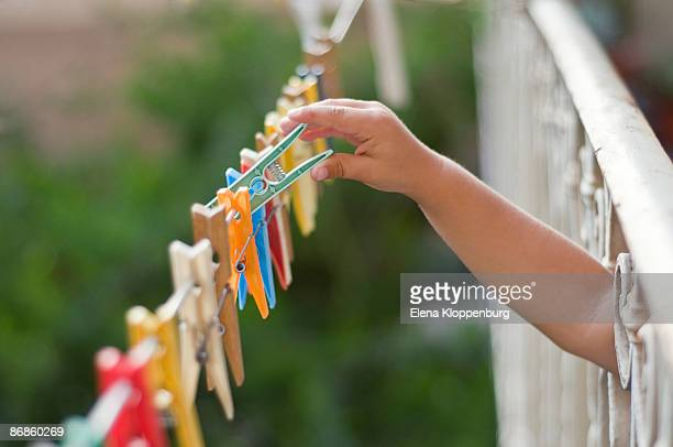 Child putting clothes pegs on a line