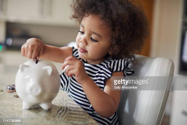 child putting coins into a piggy bank - saving stock pictures, royalty-free photos & images