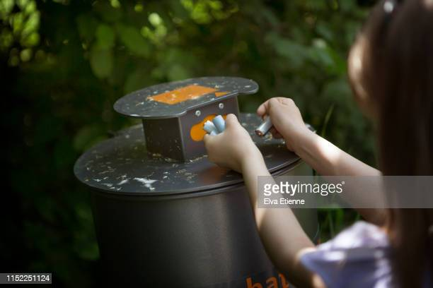 child putting old batteries into a recycling collection bin - battery stock photos and pictures