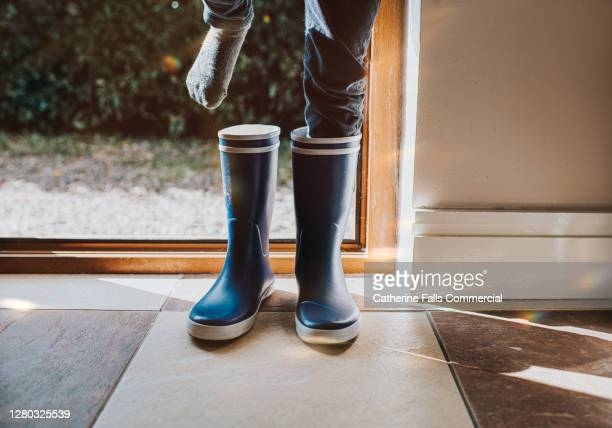 child putting on blue wellington boots - preparation stock pictures, royalty-free photos & images