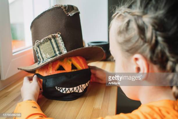 child putting protective mask on jack o'lantern for halloween - halloween stock pictures, royalty-free photos & images