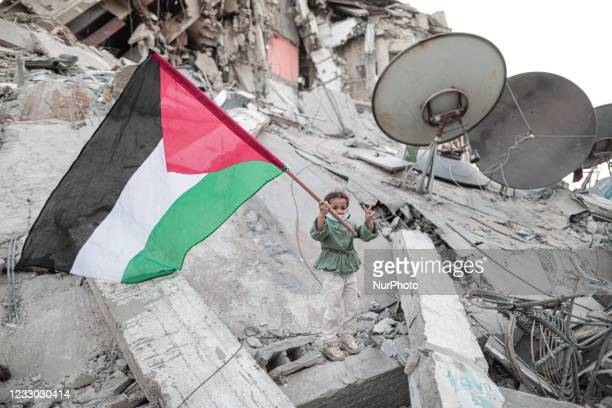 Child raises a Palestinian flag over the rubble of the destroyed Al-Shorouk building, which was destroyed by an Israeli airstrike, on May 21 in Gaza...