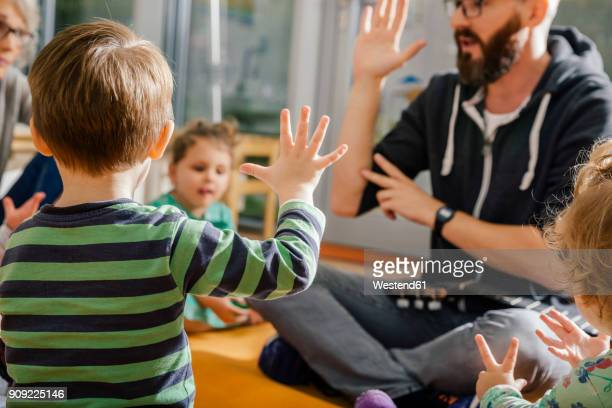 child raising hand while singing with others and teacher in kindergarten - preschool stock pictures, royalty-free photos & images