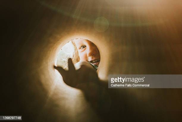 child reaching into a small hole with an outstretched hand - looking stock pictures, royalty-free photos & images