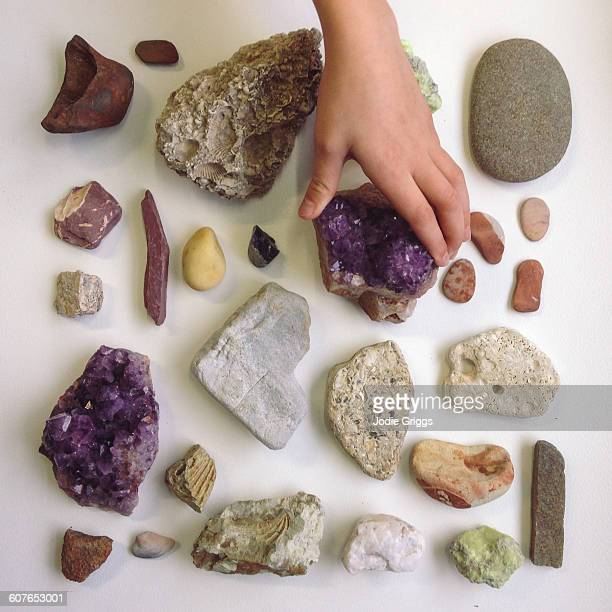 Child reaching out to touch collection of rocks
