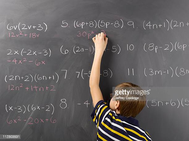 Child Reaching to Complete Equation on Blackboard
