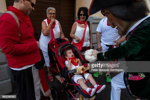 A child reacts as Caravinagre 'Vinegar face' kiliki holds his sponge during the Comparsa de Gigantes y Cabezudos or Giants and Big Heads parade on...