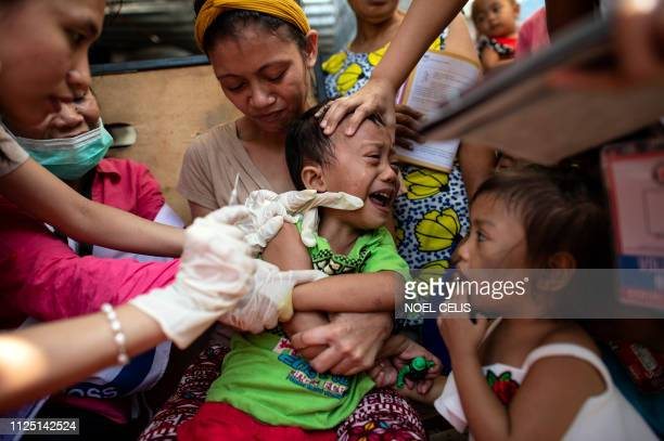 TOPSHOT A child reacts during a Philippine Read Cross Measles Outbreak Vaccination Response in Baseco compound a slum area in Manila on February 16...