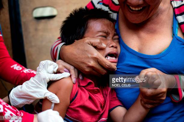 A child reacts during a Philippine Read Cross Measles Outbreak Vaccination Response in Baseco compound a slum area in Manila on February 16 2019 A...