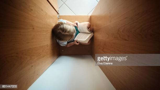 Child reading a book in a cozy space inside a wardrobe