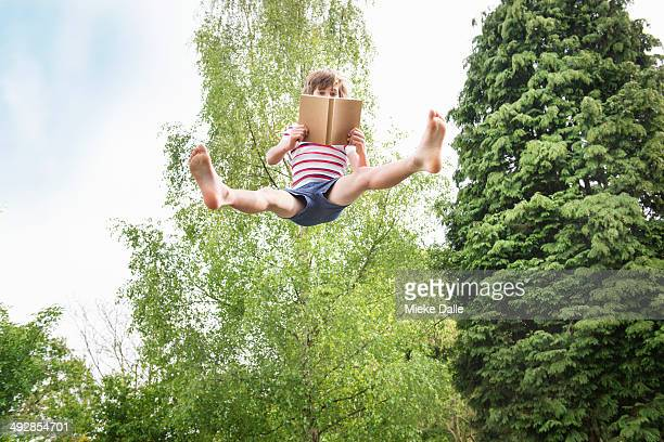 Child reading a book while jumping in the air