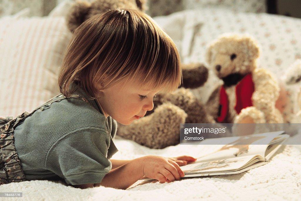 Child reading in bed : Stockfoto