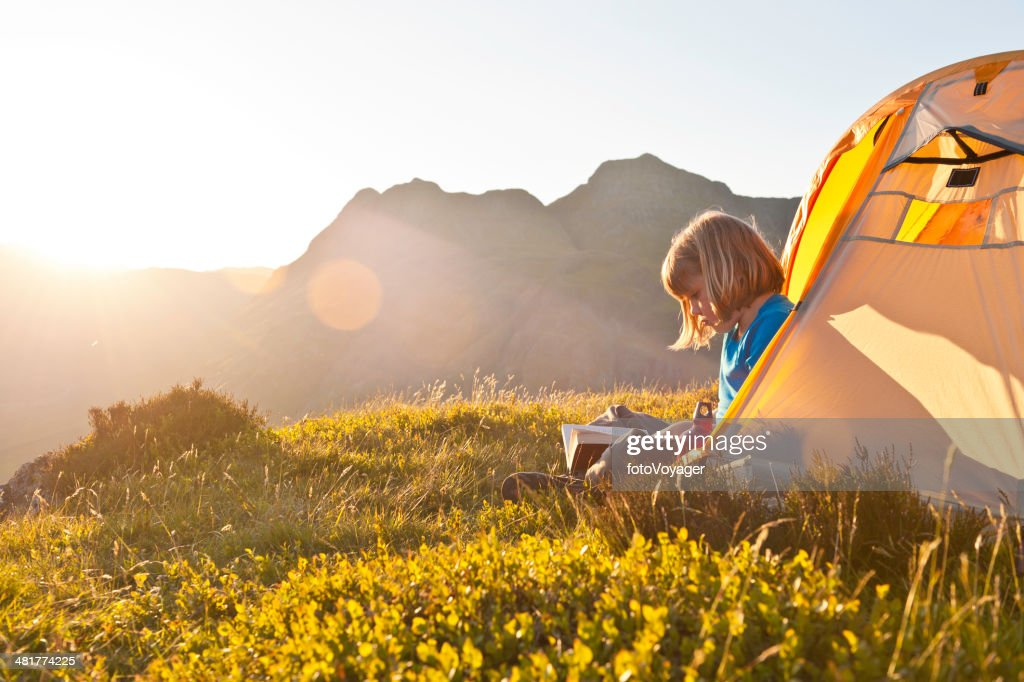 Child reading in idyllic summer sunset light camping in mountains : Stock Photo